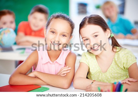 Cute girls looking at camera at lesson on background of their classmates - stock photo