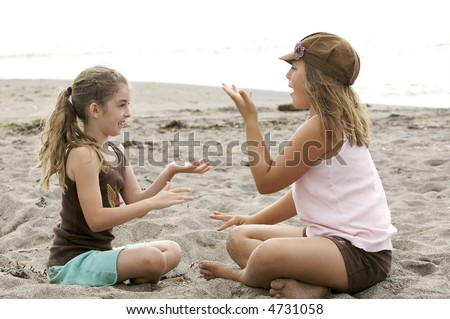 Cute girls playing a clapping game at the beach in the sand - stock photo
