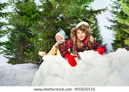Cute girls playing the snowballs on a winter's day - stock photo