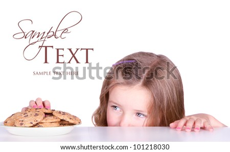 Cute girls steals cookies from a plate isolated on white - stock photo