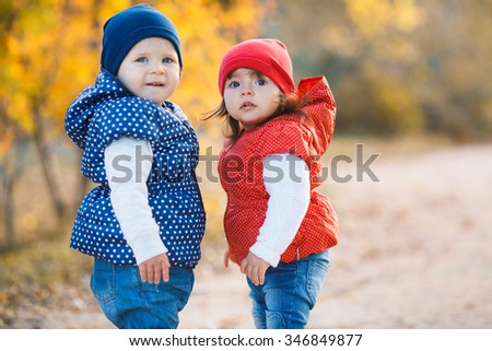 Cute girls walk in the rays of the autumn sun Outdoors shot. Two cheerful little girls playing on the lake in warm autumn day. Fall lifestyle portrait of children having fun
