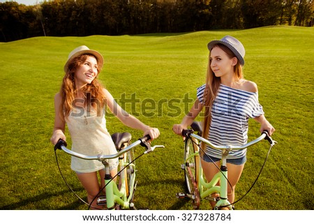 cute girls with a hats walking with a bicycle on lawn - stock photo