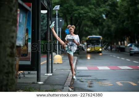 Cute girls with tablet on a bus station with a leg split - stock photo