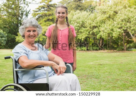 Cute granddaughter with grandmother in her wheelchair smiling at camera in park - stock photo