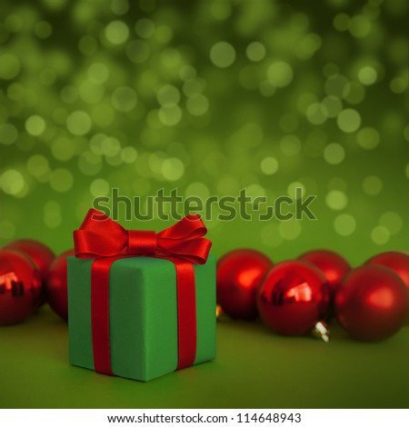 Cute green gift with red christmas balls on green abstract light background