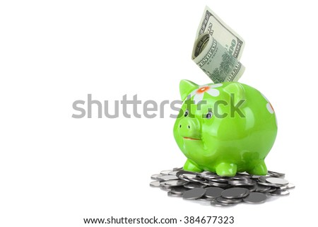 cute green piggy Bank with a picture of the flower stands on a pile of silver coins isolated on white background