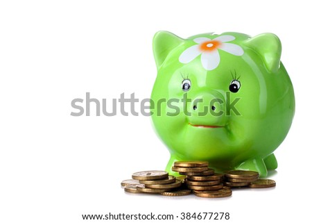cute green piggy Bank with painted flower stands on a heap of gold coins isolated on white background