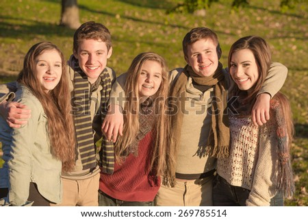 Cute group of European teenagers embracing each other - stock photo