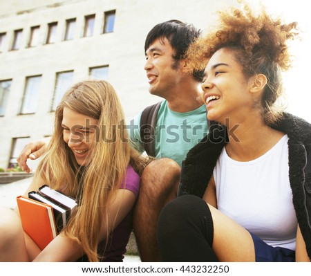 cute group teenages at the building of university - stock photo