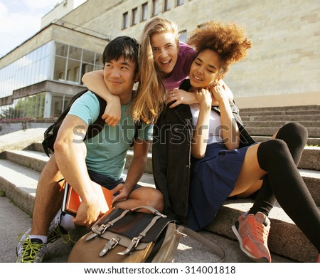 cute group teenages at the building of university with books huggings, smiling, back to school - stock photo