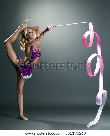 Cute gymnast dancing with ribbon, on gray backdrop