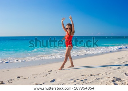 Cute gymnastic little girl doing her exercises on tropical beach - stock photo