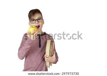 Cute handsome boy in glasses with stack of books under his arm eating an apple isolated on white background with copy space for text - stock photo