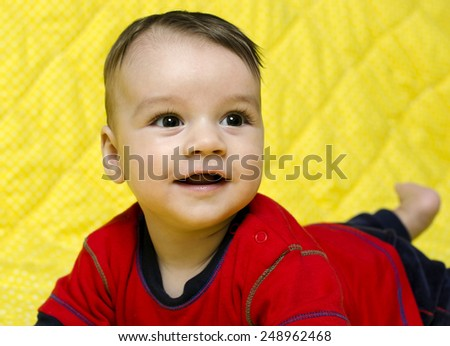 Cute happy baby boy. Baby lying on his tummy smiling and looking up. - stock photo