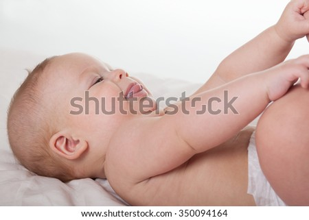 Cute happy baby boy girl kid lying and playing with its foot