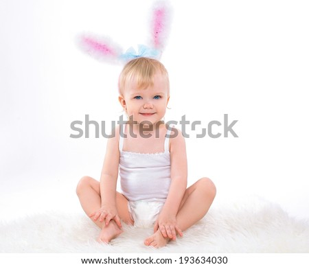 Cute happy baby dressed in easter bunny ears on a white background - stock photo