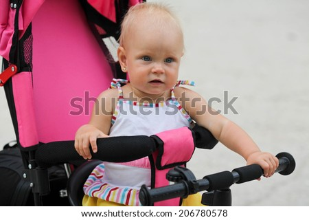 Cute happy baby girl riding her first bicycle  - stock photo