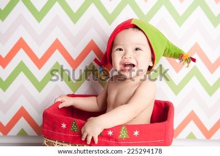 Cute happy baby in red Christmas hat sitting in a basket on defocused colourful background - stock photo