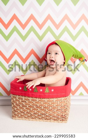 Cute happy baby in red Christmas hat sitting in a basket on defocused colourful background