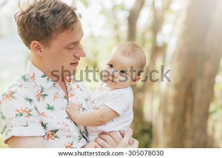Cute happy baby laughing with his father  having fun outdoors in spring park against natural green background. Father in focus. family shot  - stock photo