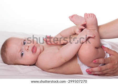 Cute happy baby lying and mother's hands massaging it's body - stock photo