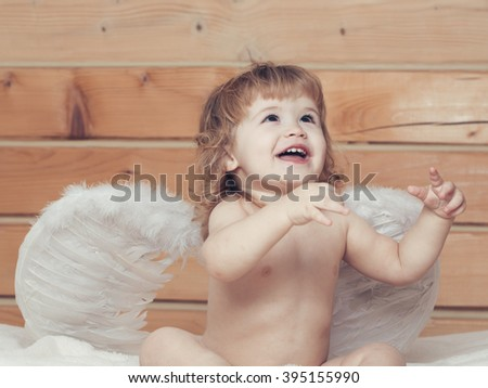 Cute happy beautiful playful child boy with wet hair sitting in hothouse bath white fluffy towel naked indoor on wooden background in feathered angel wings, horizontal picture - stock photo
