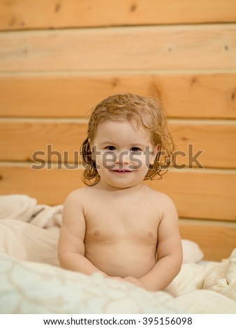 Cute happy beautiful smiling playful child boy with wet hair sitting in hothouse bath white fluffy towel naked indoor on wooden background, vertical picture - stock photo