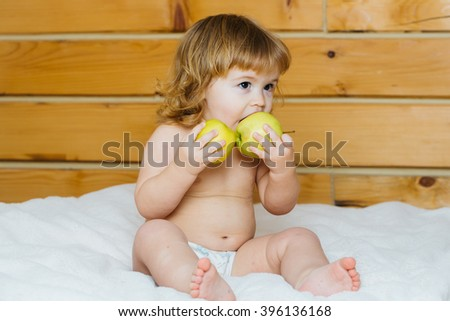 Cute happy beautiful smiling playful child boy with wet hair sitting in hothouse bath white fluffy towel naked indoor on wooden background eating apples, horizontal picture - stock photo