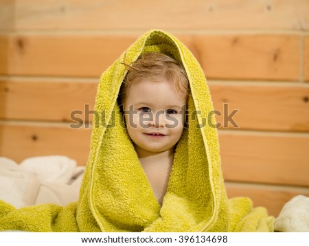 Cute happy beautiful smiling playful child boy with wet hair sitting in hothouse bath yellow fluffy towel naked indoor on wooden background, horizontal picture - stock photo