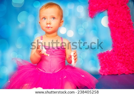 Cute happy blond baby girl in pink tutu and flower head band standing on blue background by smashed double tier heart decorated pink fondant iced cake with dirty sticky hands from messy crumb cake