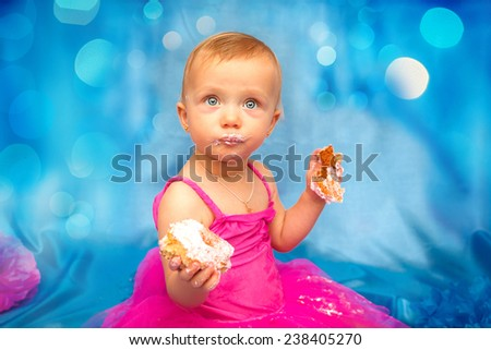 Cute happy blond baby girl in pink tutu and flower head band standing on blue background by smashed double tier heart decorated pink fondant iced cake with dirty sticky hands from messy crumb cake - stock photo
