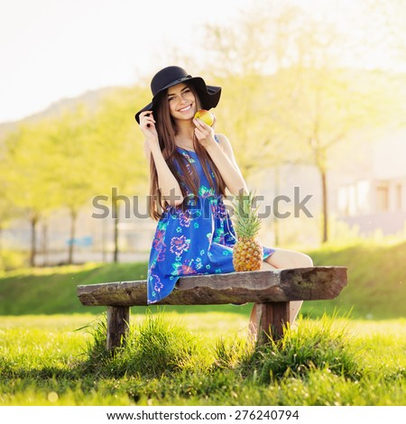 Cute happy bohemian young woman in blue floral dress and fedora hat sitting on a bench in park on sunny summer day. Portrait of boho teenage girl. Natural light, retouched, square format. - stock photo