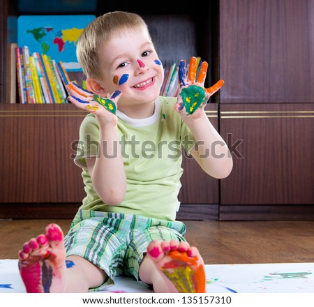 Cute happy boy painting with colorful paints