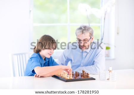 Cute happy boy playing chess with his grandfather sitting at a window in a white living room - stock photo