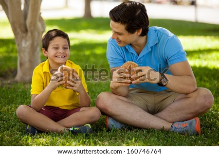 Cute happy boy spending some time with his dad and eating a hamburger in a park - stock photo
