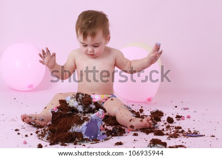 Cute happy brunette baby girl in pink pants sitting on pink background by birthday party double tier pink and purple butter iced chocolate cake holding her dirty sticky hands from messy cake in air.