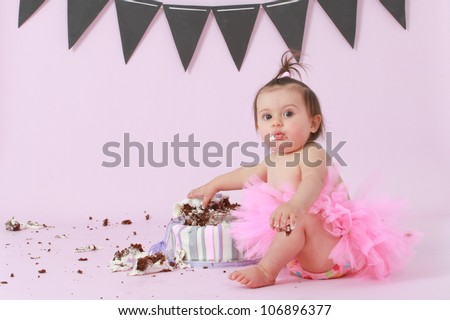 Cute happy brunette baby girl in pink tutu sitting on background by her double tier pink and purple fondant iced birthday party cake reaching out touching and destroying it looking at camera surprised