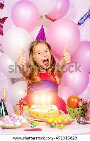 Cute happy child girl enjoys her birthday. Celebration, life events. Happy birthday.