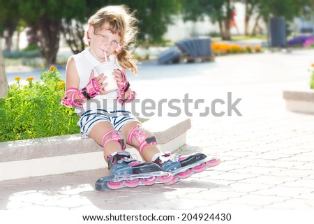 cute happy child girl roller skating on natural background - stock photo