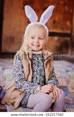 cute happy child girl wearing bunny ears for easter  - stock photo