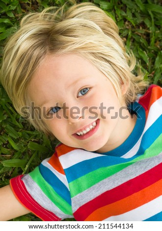Cute happy child in colorful t-shirt lying on grass - stock photo