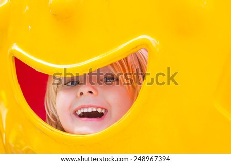 Cute happy child peeking in a playground - stock photo
