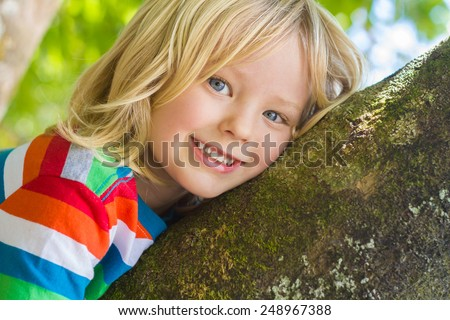 Cute happy child relaxing outdoors in a tree - stock photo
