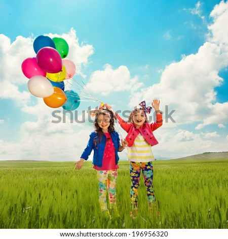 Cute happy children with balloons walking on summer field. Happiness, friendship, fashionable concept. - stock photo