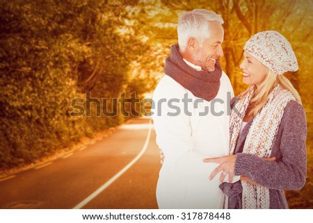 Cute happy couple romancing against country road - stock photo