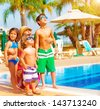 Cute happy family having fun near pool on luxury tropical resort, mother with children looking up in sky, summer holidays, love concept - stock photo