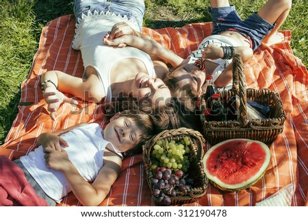 cute happy family on picnic laying on green grass mother and kids, warm summer vacations - stock photo