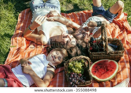 cute happy family on picnic laying on green grass mother and kids, warm summer vacations close up, brother and sister - stock photo
