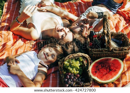 cute happy family on picnic laying on green grass mother and kids, warm summer vacations close up, brother and sister together - stock photo