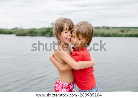 Cute happy fraternal twins enjoying their time at the beach. Brother and sister hugging. Friends having fun at summertime. Nice day with family at the lake - stock photo